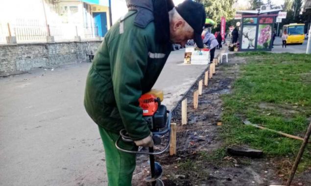 На столичных Березняках коммунальщики пытаются оградить зеленые зоны от автомобилей деревянными столбиками